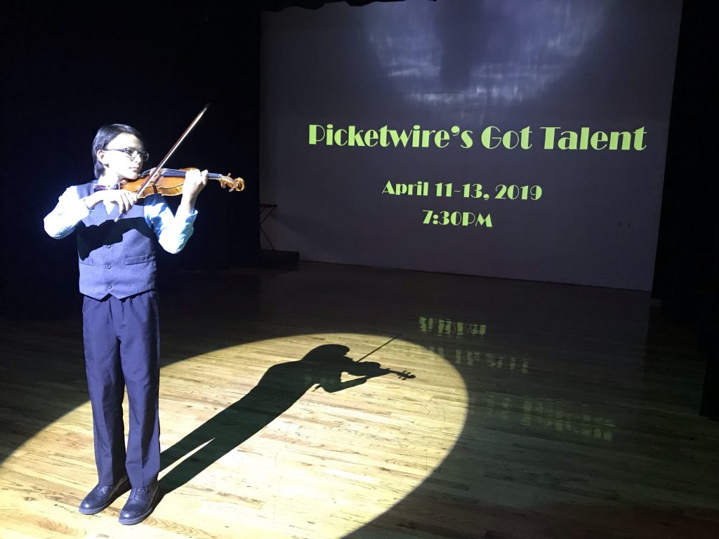 Christain holding violin as winner of PGT